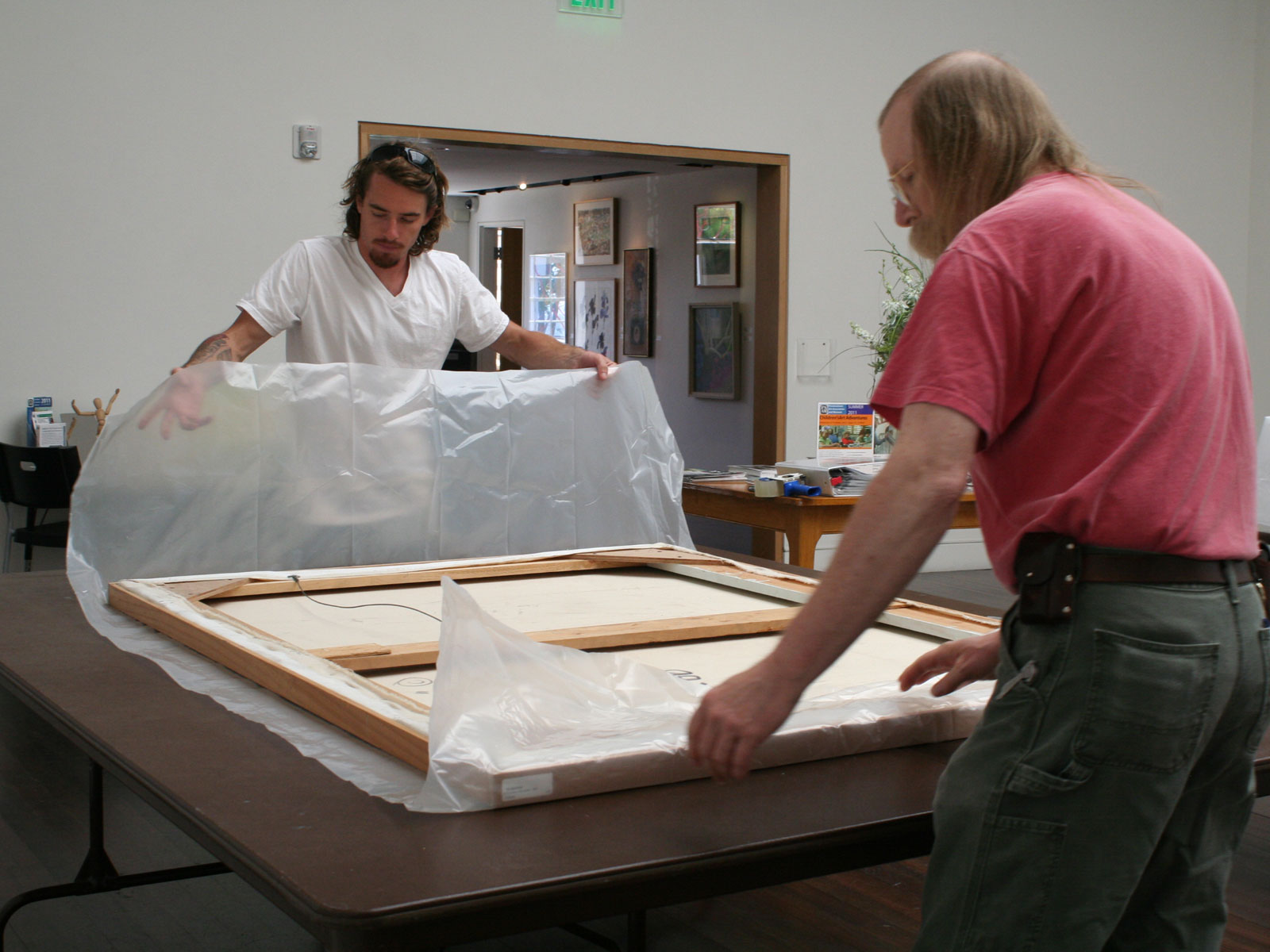 Intern Colin helps PAAM Archivist James Zimmerman wrap a painting in plastic for safe transportation