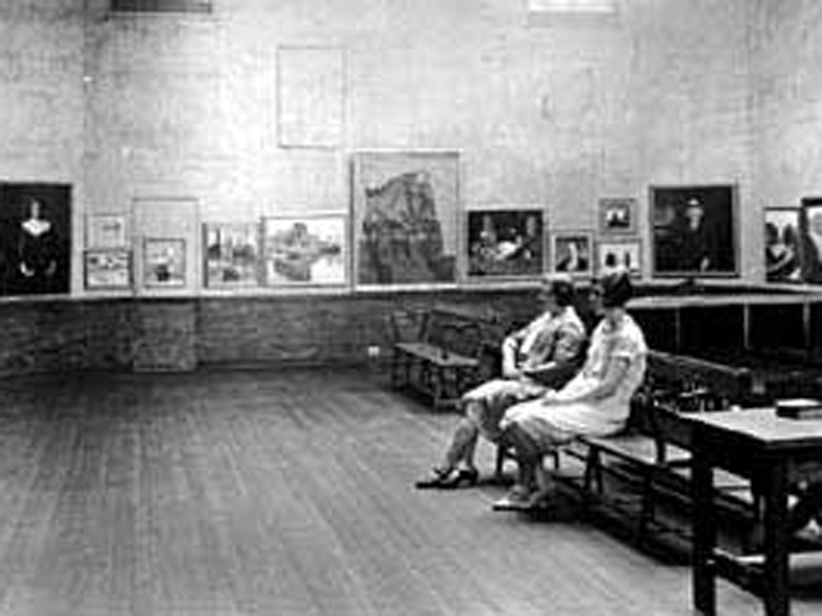 archival image of two women sitting on a bench in the museum looking at an exhibition